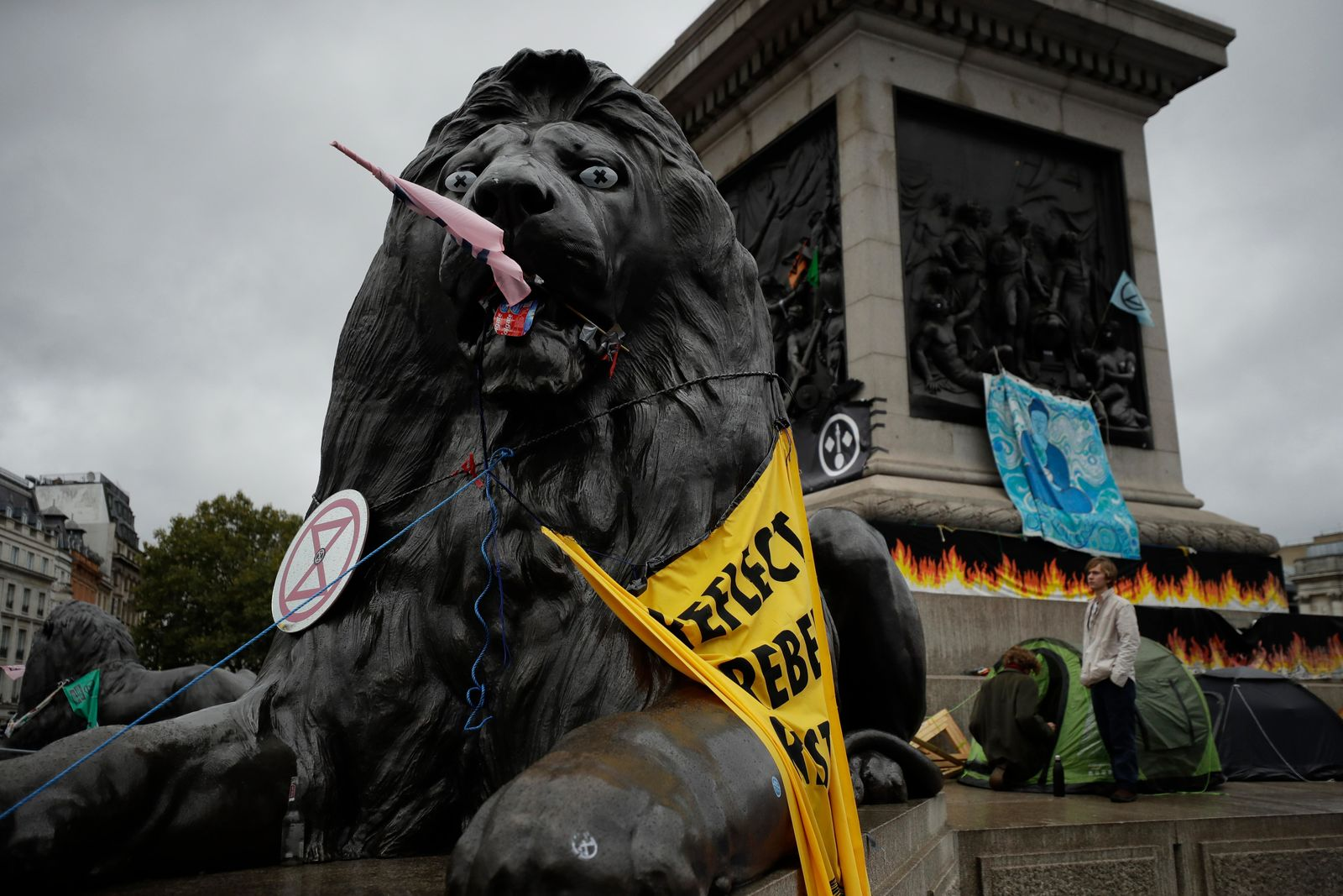 A lion statue is decorated by Extinction Rebellion climate change protesters in Trafalgar Square, London, Friday, Oct. 11, 2019.{ } (AP Photo/Matt Dunham)