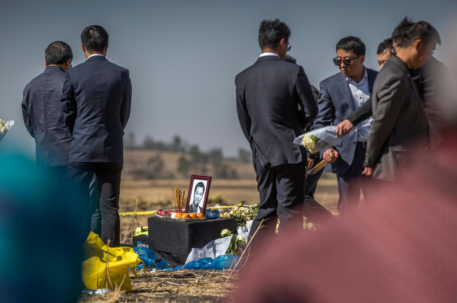 A photograph of a Chinese crash victim is placed next to incense and an offering of fruit, as relatives mourn and grieve at the scene where the Ethiopian Airlines Boeing 737 Max 8 crashed shortly after takeoff on Sunday killing all 157 on board, near Bishoftu, south-east of Addis Ababa, in Ethiopia Friday, March 15.. (AP Photo/Mulugeta Ayene)