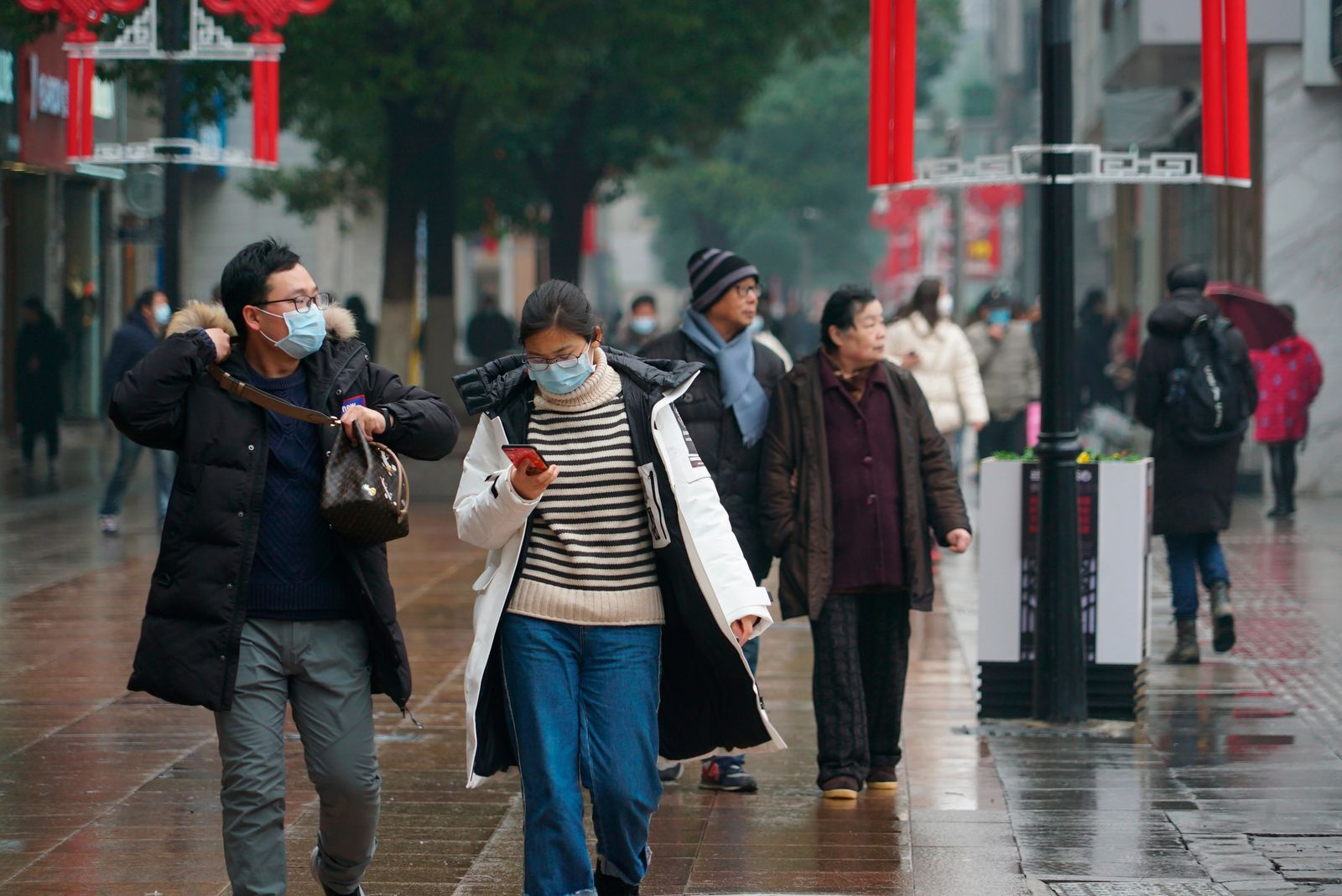 Masked pedestrians walk down a shopping street in downtown Wuhan, China, Wednesday,  Jan. 22, 2020. The number of cases of a new coronavirus from Wuhan has risen over 400 in China and the death toll to 9, Chinese health authorities said Wednesday. (AP Photo/Dake Kang)