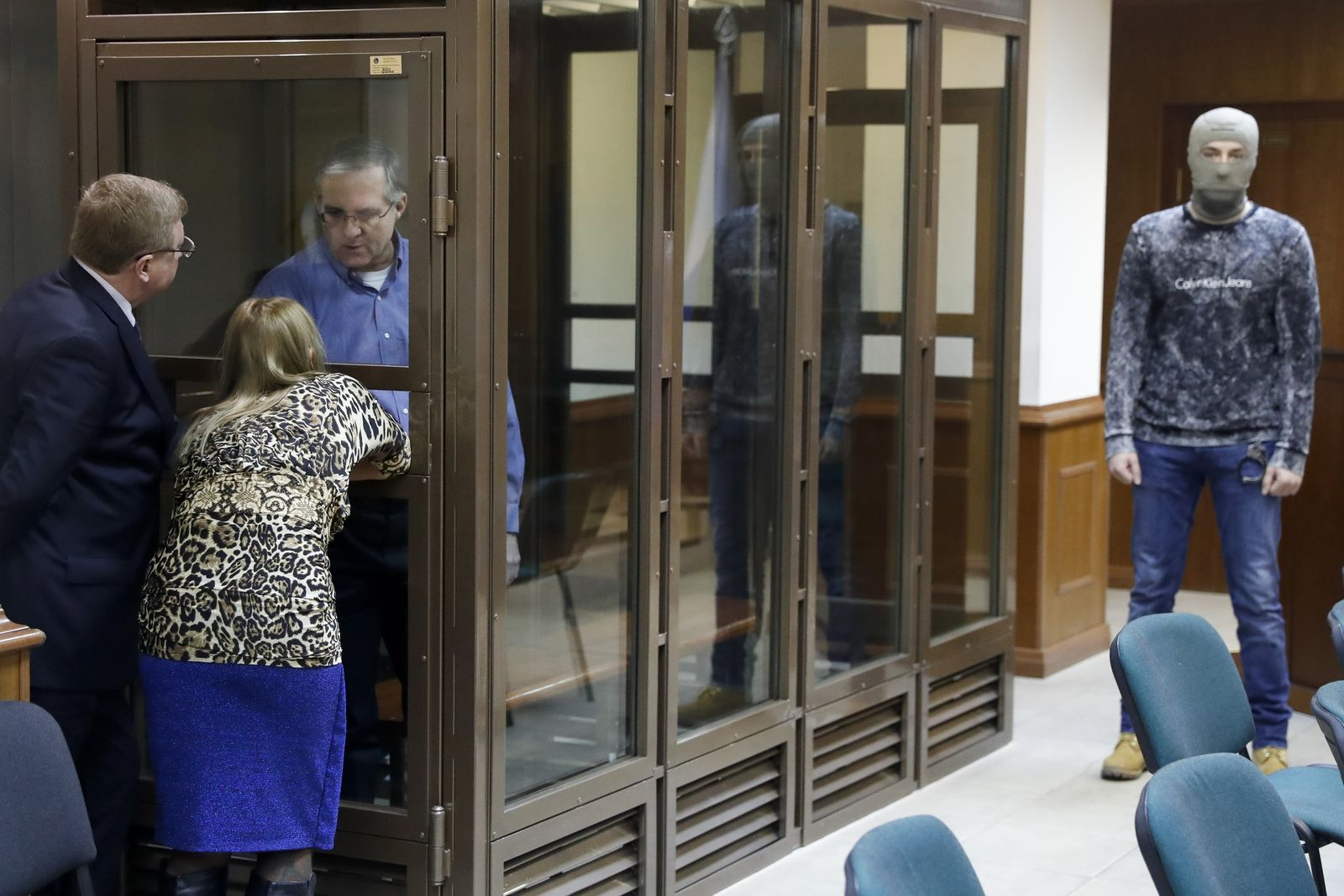 Paul Whelan, a former U.S. Marine, who was arrested in Moscow at the end of last year looks through a cage's glass as he speaks to his lawyers in a court room in Moscow, Russia, Tuesday, Jan. 22, 2019. (AP Photo/Pavel Golovkin)