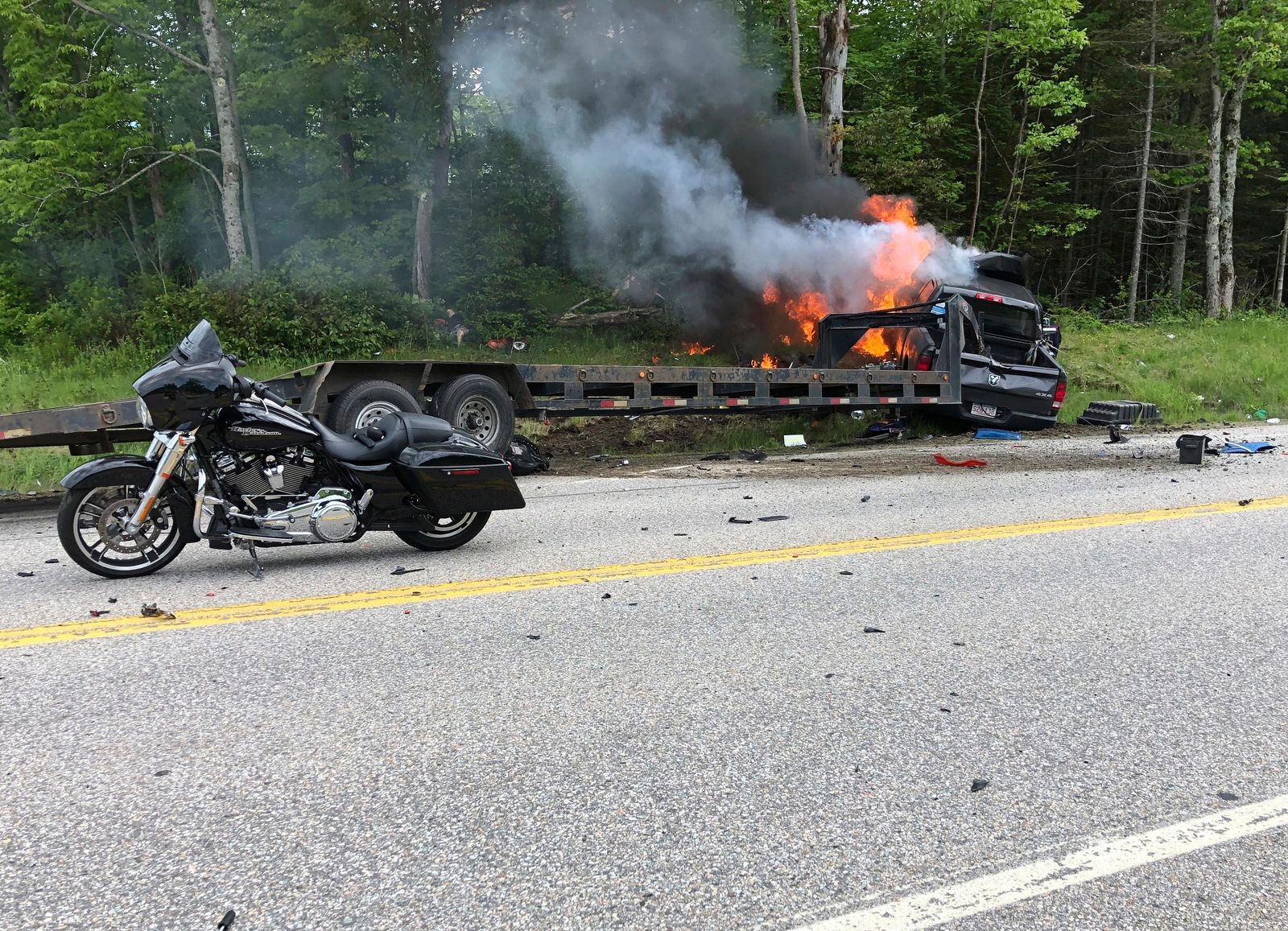 This photo provided by Miranda Thompson shows the scene where several motorcycles and a pickup truck collided on a rural, two-lane highway Friday, June 21, 2019 in Randolph, N.H.  New Hampshire State Police said a 2016 Dodge 2500 pickup truck collided with the riders on U.S. 2 Friday evening. The cause of the deadly collision is not yet known. The pickup truck was on fire when emergency crews arrived.  (Miranda Thompson via AP)
