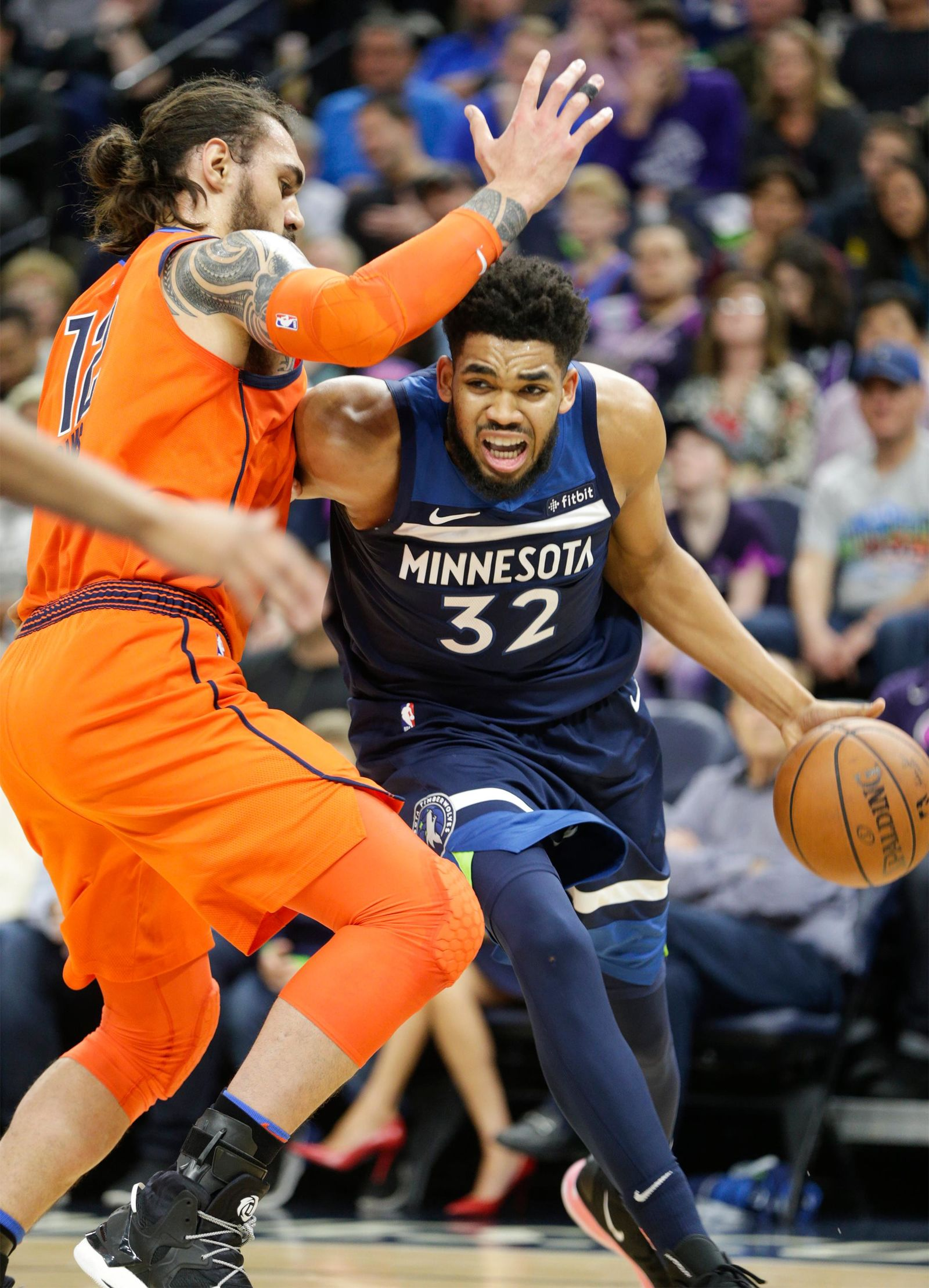 Minnesota Timberwolves center Karl-Anthony Towns (32) drives against Oklahoma City Thunder center Steven Adams, of New Zealand, (12) during the first half of a NBA basketball game Sunday, April 7, 2019, in Minneapolis. (AP Photo/Paul Battaglia)