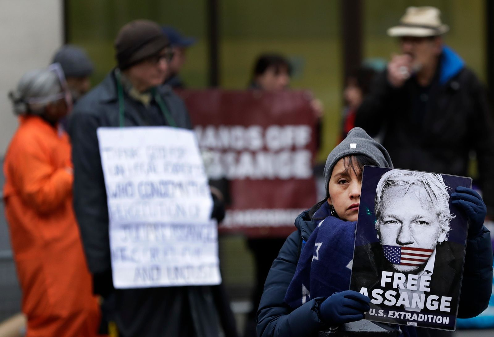 Demonstrators supporting Julian Assange hold banners outside Westminster Magistrates Court in London, Thursday, Jan. 23, 2020.{ } (AP Photo/Kirsty Wigglesworth)