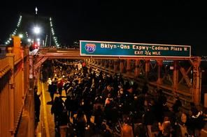 A group of protesters rallying against a grand jury's decision not to indict the police officer involved in the death of Eric Garner marches across the eastbound traffic lanes of the Brooklyn Bridge in the early morning hours of Thursday, Dec. 4, 2014, in New York. (AP Photo/Jason DeCrow)