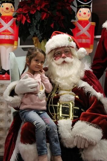 Santa poses with a little girl during the 2018 Jingle Bell Block Hop. (Credit: Savannah Holly Days)