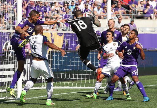 Real Salt Lake goalkeeper Nick Rimando (18) stops a goal-attempt as several Orlando City SC players watch during an MLS soccer game in Orlando, Fla., Sunday, March 6, 2016. (Stephen M. Dowell/Orlando Sentinel via AP) MANDATORY CREDIT