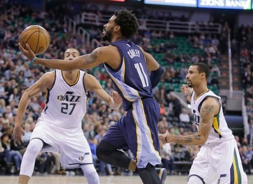 Memphis Grizzlies guard Mike Conley (11) shoots a layup as Utah Jazz's Rudy Gobert (27) and George Hill, right, watch during the first half in an NBA basketball game Saturday, Jan. 28, 2017, in Salt Lake City. (AP Photo/Rick Bowmer)