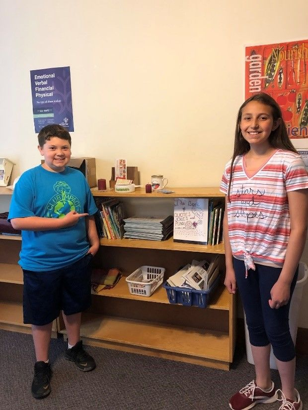 Fifth graders, Colin and Kayla, in front of a display where their book will be available to Webster families at Hope Ministries.{ }(Photo: Webster CSD)
