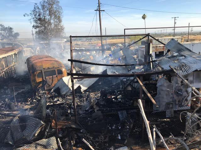 Firefighters battle a fire in rural Oildale, Calif., on Saturday, Aug. 17, 2019. About 40-50 cars were burned in the fire.