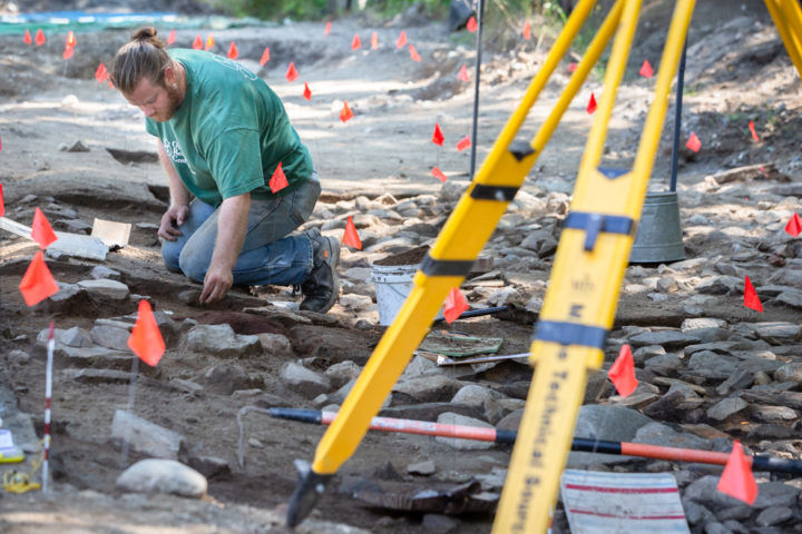Eric Trautman-Mosher, a graduate student, works at an archaeological dig site under the River Road in Windham last week. Trautman-Mosher is part of a team looking for the remains of a colonial-era fort under the road. Troy R. Bennett | BDN