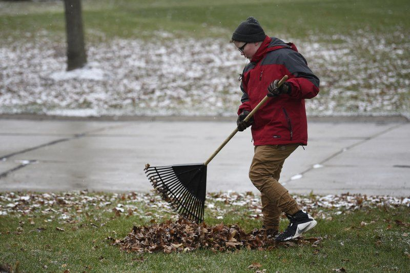 "In this Thursday, Nov. 29, 2018 photo, Kaleb Klakulak rakes leaves in Rochester Hills, Mich., as he raises money for a headstone for his best friend Kenneth ""K.J."" Gross, who died of cancer last year. (Max Ortiz/Detroit News via AP)"