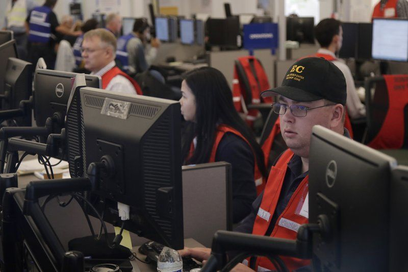 FILE - In this Oct. 10, 2019, file photo, Pacific Gas & Electric employees work in the PG&E Emergency Operations Center in San Francisco.{ } (AP Photo/Jeff Chiu, File)