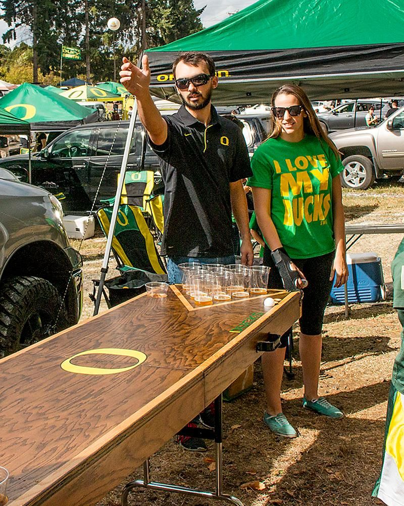 While tailgating across from Autzen Stadium on Saturday afternoon, Jayson Shaver throws an attempt during a round of beer pong as his partner Amy Fust watches. Katie Pietzold, Oregon News Lab