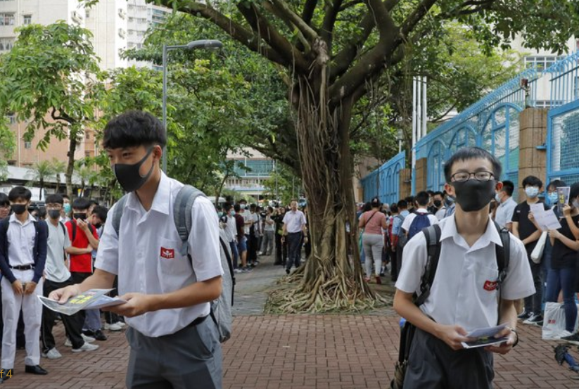 High school students wearing masks, deliver leaflets to support the school boycott, in Hong Kong, Wednesday, Sept. 4, 2019.. (AP Photo/Kin Cheung)