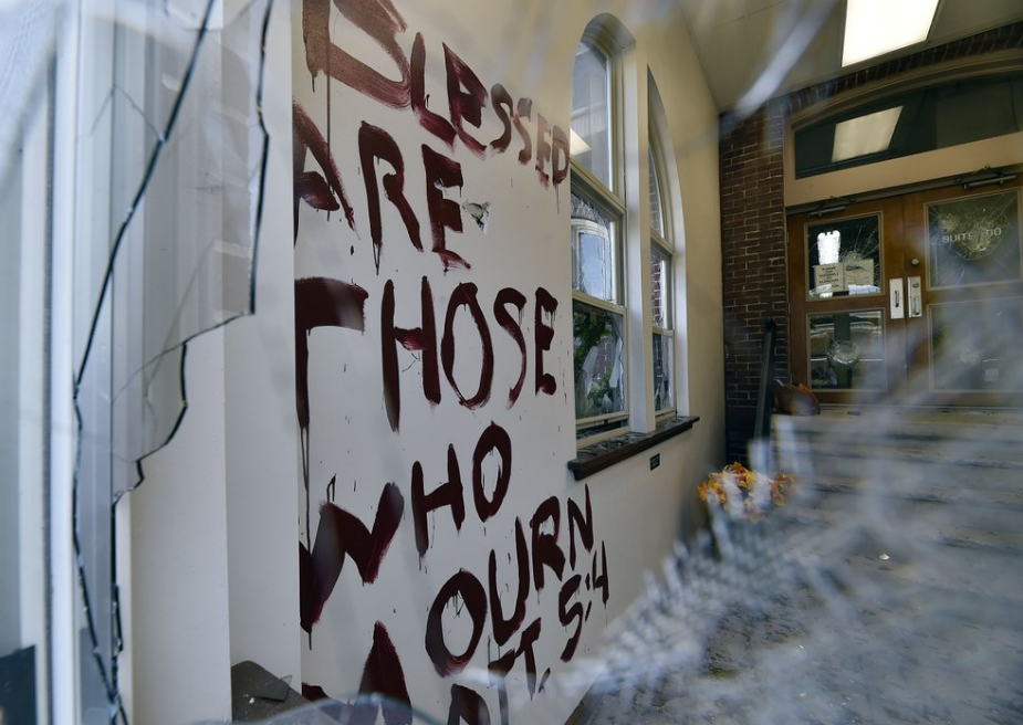 A biblical quote from Matthew 5:4 was painted on the wall at the Wilkes-Barre, Pa., Planned Parenthood office which can be seen through smashed windows Monday, Aug. 12, 2019. Officials say a man broke into a Planned Parenthood office in northeastern Pennsylvania, smashing glass doors and painting graffiti on the walls. (Aimee Dilger/The Times Leader via AP)