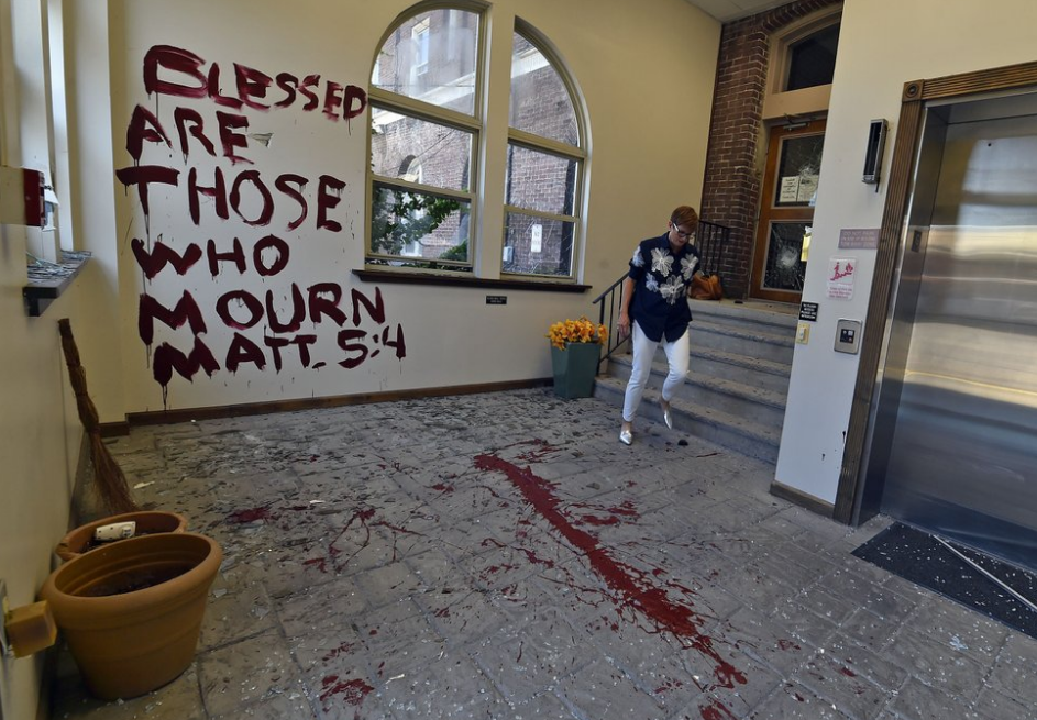 Melissa Reed from Planned Parenthood leaves the area that was vandalized overnight in Wilkes-Barre, Pa. A man smashed doors and windows left a burnt book and wrote on the wall with paint Monday, Aug. 12, 2019 (Aimee Dilger/The Times Leader via AP)