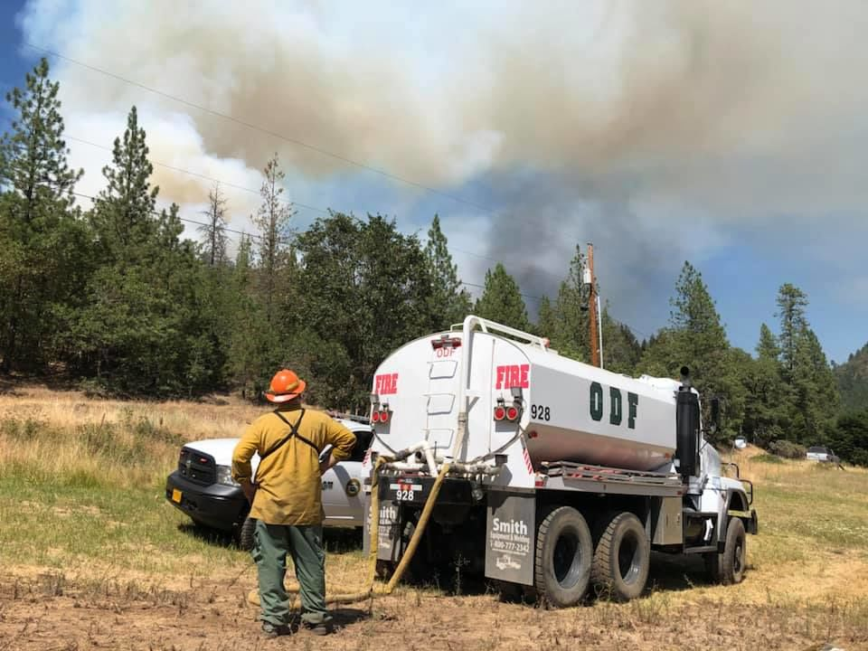 A firefighter stands next to an ODF truck, looking at a column of smoke from the fire on East Evans Creek Road. (Courtesy ODF)