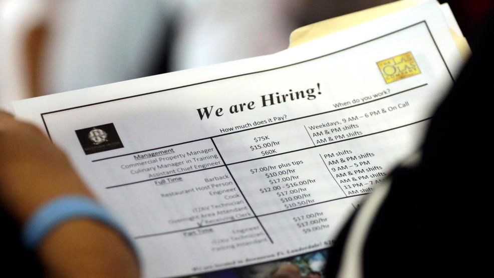 FILE In this June 21, 2018 file photo, a job applicant looks at job listings for the Riverside Hotel at a job fair hosted by Job News South Florida, in Sunrise, Fla. (AP Photo/Lynne Sladky)